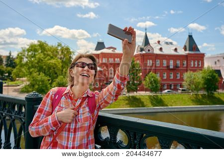 Happy cheerful woman making selfie on the background of historical buildings. Russia, Orel city orlik embankment state bank building
