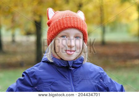 Cheerful girl shows tongue, the child is dressed in a funny knitted warm hat with ears, looks like a fox. Autumn, outdoors portrait.