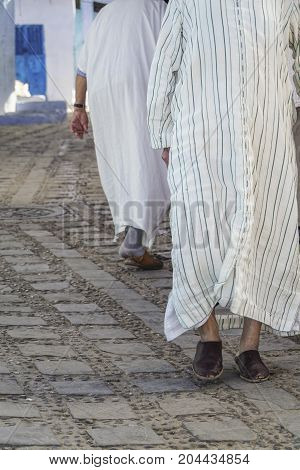 unrecognisable arabic men walking in their traditional clothes thobe