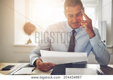 Smiling Mature Businessman Reading Documents At His Office Desk