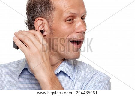 Portrait of happy man shaving his ear with trimmer