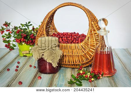 Basket of cranberries on a blue wooden textured background and a sprig of cranberries, jam and red drink.