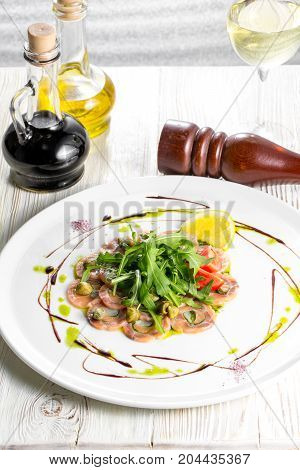Salmon carpaccio with arugula leaves and sticky balsamic vinegar.