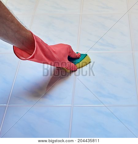 Closeup of hand in glove with sponge cleaning a tile in the bathroom, image with square aspect ratio
