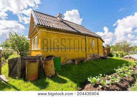 Rural landscape with small wooden house and vegetable garden in sunny summer day