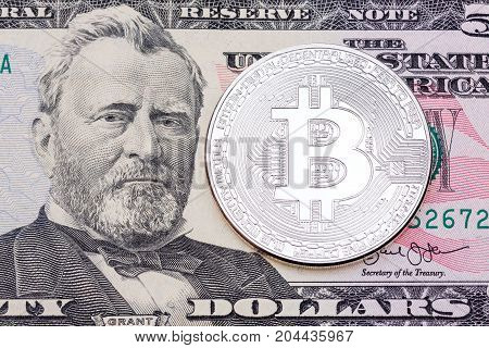 SIlver bitcoin on fifty dollas banknote. High resolution photo.
