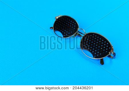 Two different type of glasses on blue background. Medical concept. Top view. Pinhole black eyeglasses help relaxing weary eyes Isolated on white background. Classic Fashion optical eyeglasses.