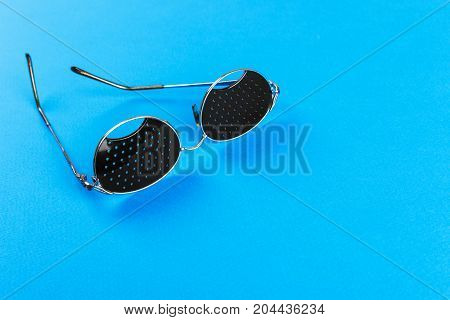 Black pinhole glasses on blue background. Medical concept. Top view.