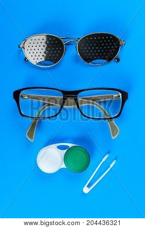 Medical concept. A set of accessories for sight. Top view. Pinhole glasses lenses with container and glasses for sight.