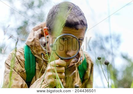 Picture of environmentalist man with magnifying glass in summer forest