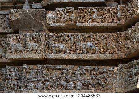 Mysore India - October 27 2013: Close up of three brownish stone friezes on outside wall of central shrine called Trikuta at Chennakesave temple in somanathpur. LInes of ducks monsters war scene