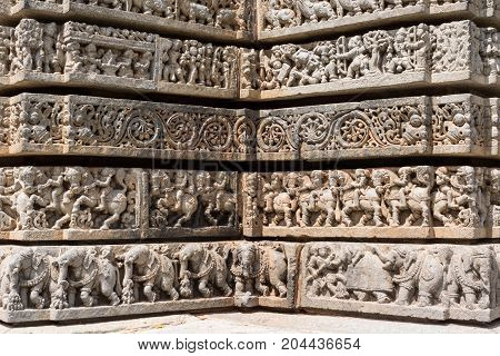 Mysore India - October 27 2013: Series of four friezes on outside wall of central shrine called Trikuta at Chennakesave temple in somanathpur. Warriors on horses elephants decorative infantry.