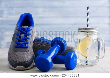 Sport composition with gray sneakers with blue shoelaces blue dumbbells mason jar with water lemon and blue straws on gray background. Concept healthy lifestyle detox diet sport.