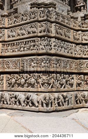 Mysore India - October 27 2013: Series of six corner friezes on outside wall of central shrine called Trikuta at Chennakesave temple in somanathpur. Warriors on horses elephants infantry.