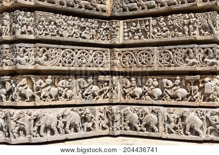 Mysore India - October 27 2013: Series of four corner friezes on outside wall of central shrine called Trikuta at Chennakesave temple in somanathpur. Warriors on horses elephants infantry.