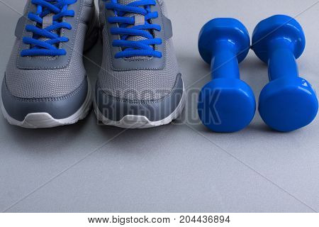 Sport equipment - gray sneakers with blue shoelaces and blue dumbbells on gray background. Concept healthy lifestyle detox diet sport.