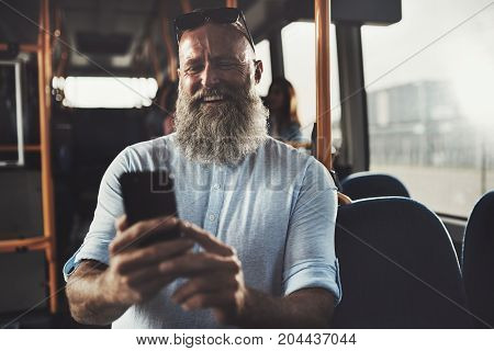Laughing Mature Man Reading Texs While Riding On A Bus