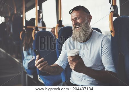 Smiling mature man with a long beard sitting on a bus reading text messages on his cellphone during his morning commute