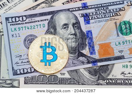 Yellow blue bitcoin on hundred banknotes background. High resolution photo.