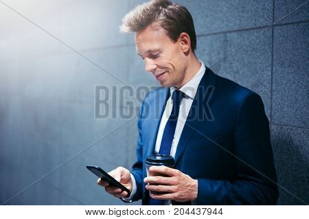 Smiling Businessman Reading Messages While Waiting For A Subway