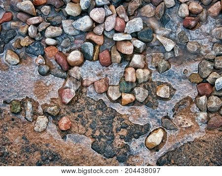 Ice melting on pavement and stones, creating interesting natural textures
