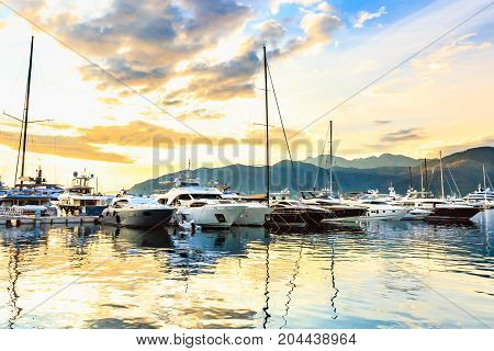 Luxury yachts and sailing boats docked in marina called Porto Montenegro, Tivat. Port in Mediterranean sea at sunset. Fashionable vacation.