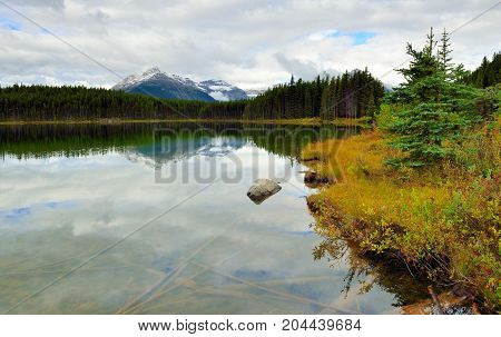 Beautiful High Mountains Of The Canadian Rockies Reflecting In An Alpine Lake Along The Icefields Pa