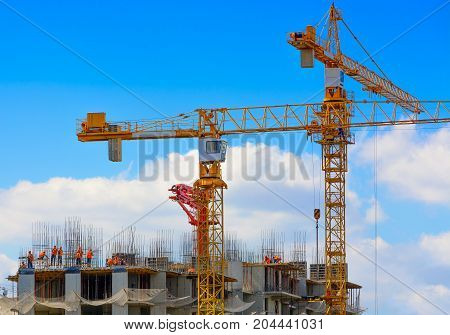 Orange tower Cranes and workers at construction of residental building against blue sky in sunny day