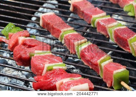Raw beef brochette on the rack of a barbecue