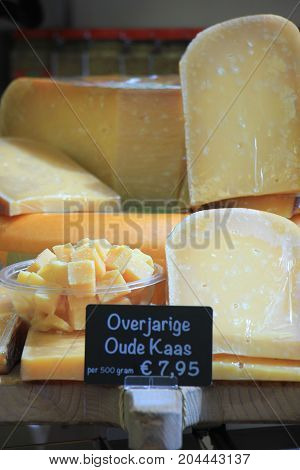 Traditional Dutch cheeses on display on a market stall Text on tag: product information in Dutch: very matured old cheese