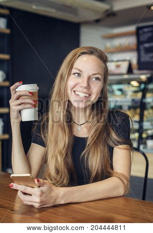 Beautiful woman laughing holding a cup of coffee and a cell phone