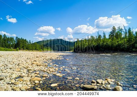 a mountain river with a stone bottom, a valley of a taiga river, yakutia,