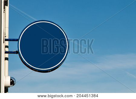Generic blue round sign attached to a wall against blue sky background. Insert your own custom text or graphics.