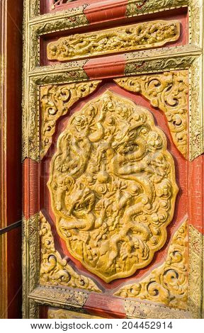 Beijing, China - Oct 30, 2016: Decorative door carving with dragon motif in relief at the Hall of Supreme Harmony (Taihedian). Forbidden City (Gu Gong, Palace Museum).