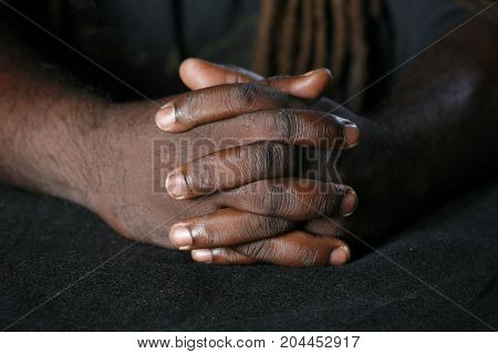 Closeup of hands of African American man with dreadlocks hairstyle on background