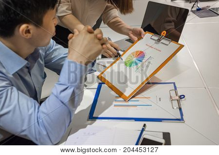 Asian manager reviewing the income of company