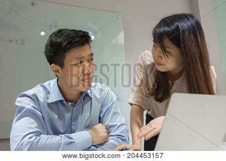 Young office lady asking her workmate for help