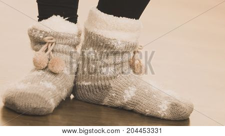 Fashion clothing winter time concept. Woman feet wearing woolen warm sock on floor.