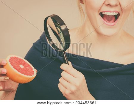 Woman Holding Magniferlooking Grapefruit