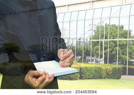 Business man with book writing job on glass office background