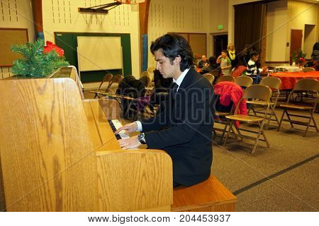 JOLIET, ILLINOIS / UNITED STATES - DECEMBER 28, 2015: A handsome young man plays the piano at a music recital at the Church of Jesus Christ of Latter-day Saints.