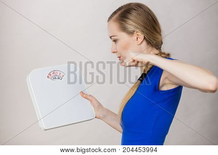 Angry Woman Holding Bathroom Scale Machine