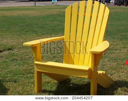 Sunshine yellow lawn chair against a green lawn.