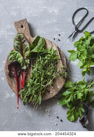 Fresh garden herbs - tarragon chard mint celery spinach thyme on a gray background top view. Flat lay