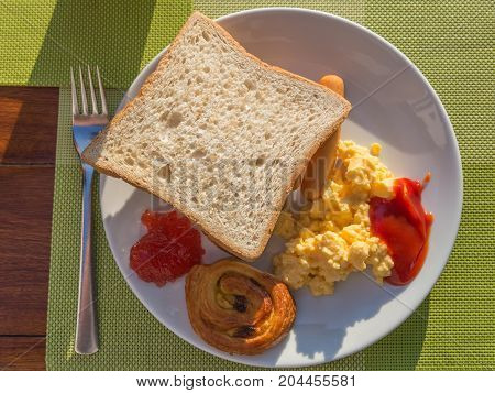 western breakfast toast scrambled egg sausage and pastry on white plate