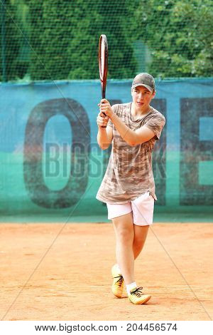 Young boy play backhand return od court