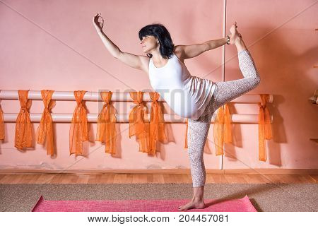 40 Week Pregnant Middle Aged Caucasian Woman Doing Yoga Exercises Bound Lord Of Dance Pose.