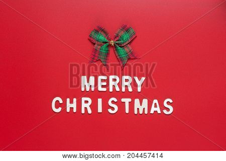 MERRY CHRISTMAS words with ribbon bow on the center of red background