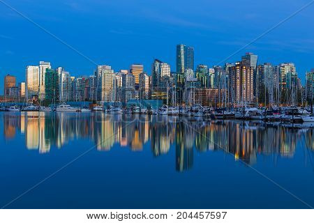 Vancouver British Columbia Canada city skyline by the marina during evening blue hour with water reflection