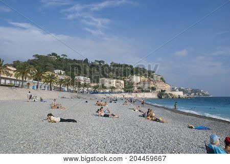 Nice, France - October 2012: People enyoing the autumn sun on pebble beach of Nice, France in 2012